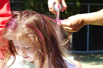 Hair highlighting - Coloring a young girl's hair with temporary spray paint