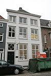 foto van Huis onder schilddak achter hoge witgepleisterde, gebosseerde lijstgevel