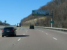 "A sign above the highway reads ""Welcome to West Virginia—Open For Business."" An adjacent sign reads ""Preston County."""