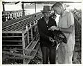 IVS Volunteer Frank Zigler and a Laotian Worker Examine a Sick Chicken at Savannakhet Poultry Station, Laos, 1966 (13875562895).jpg
