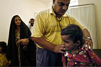 An Iraqi doctor examining a little girl