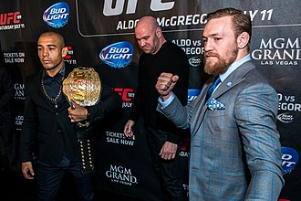 Combat sport - A photo of Conor McGregor, Jose Aldo, and Dana White at a press conference for the fight between McGregor and Aldo. This shows the two fighters posing for media, increasing revenue and interest in the fight.