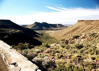 Karoo - A view from the top of the Great Escarpment in the Karoo National Park near Beaufort West, looking south across the plains of the Lower Karoo. Note the remnants of the former extent of the central plateau on the plain below the escarpment (see diagram on the right). Also note the dolerite sills which top the escarpment and mountains in the middle distance, giving these structures their characteristic flat-topped appearance.