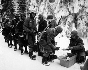 87th Infantry Division (United States) - Chow is served to American infantrymen of the 347th Infantry Regiment on their way to La Roche, Belgium, 13 January 1945.