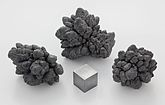 Three, dark broccoli shaped clumps of oxidised lead with grossly distended buds, and a cube of lead which has a dull silvery appearance.