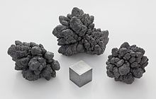 A small gray metal cube surrounded by three gray metal nuggets in front of a light gray background