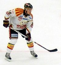An ice hockey player leaning forward with his ice hockey stick resting on the ice. He is wearing a black helmet and a white and black uniform.