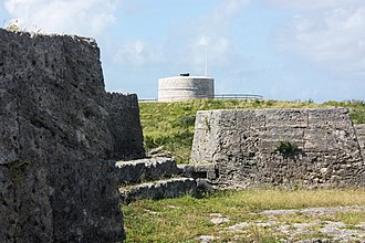 Bermuda Garrison - The effect of thirty years of evolution on the design of coastal fortifications, between the 1790s and 1822, can be discerned between Ferry Island Fort (in the foreground), with multiple guns arrayed to cover the water westward, and the Martello tower in the background, which used a single gun with 360° traverse to cover all of the surrounding area. Ferry Reach, Bermuda, 2011.