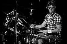 Um baterista macho, Matt Cameron, sentados por trás de um kit de bateria de tambores e pratos.