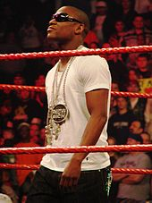 Mayweather, wearing sunglasses, white T-shirt and chains, in wrestling ring with red ropes