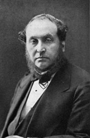 photograph of middle-aged man with bushy sideboards facing spectator, in jacket, waistcoat and bowtie