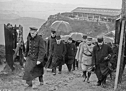 Zwart-witfoto van verschillende mannen (burgers en soldaten) die bij regenachtig weer op de top van een heuvel aankomen;  in het midden van het schot kijkt een man met wit haar, dikke donkere wenkbrauwen, een grijze snor en gekleed in een donkergekleurde jas naar de camera