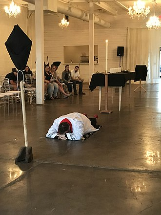 A United Methodist minister prostrates at the start of the Good Friday liturgy at Holy Family Church, in accordance with the rubrics in the Book of Worship. The processional cross is veiled in black, the liturgical colour associated with Good Friday in Methodist Churches. Minister prostrates at the start of United Methodist Good Friday liturgy.jpg