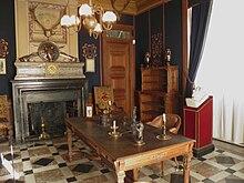salle au sol et à la cheminée couverts de marbres noir, blanc et rouge, avec une table au centre, des étagères en bois contre un mur de couleur bleu foncé et une tête en marbre posé sur un pupitre en bois