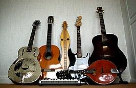 Verschillende sorten gitaren (van links naar recht: resonator-, klassieke, elektrische en westerngitaar). Er zijn ook: in het midden een dulcimer en, horizontaal liggend, een MIDI-keyboard en een mandoline.