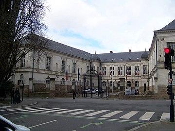 Cour encadrée par trois bâtiments, et fermée par une grille avec portail.