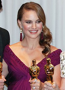 An image of a smiling woman with light brown hair in her 20s. She is wearing a purple dress and is holding a golden statue.