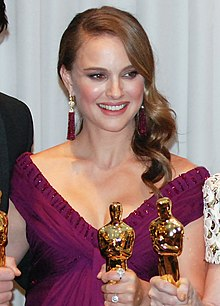 A young woman with brown hair dangling to her left in a V-neck purple dress holding one of the golden statuettes seen above