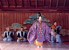 Acteur debout en tenue traditionnelle violette, masque blanc souriant. Trois musiciens visibles en arrière plan.
