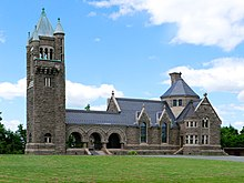 Dark stone-faced building with tall bell tower at left. Arches connect to the main receiving rooms and chapel; roof is a slate blue color.