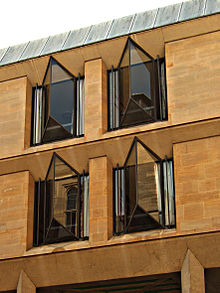 Four windows from a two-storey stone building projecting in a V-shape