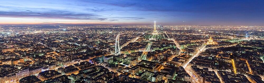 Alacakaranlıkta Maine-Montparnasse kulesinden Paris  ortada Eyfel Kulesi, kulenin önünde Champ de Mars, Harp Okulu ve UNESCO, Breteuil Meydanı, arkasında La Défense, sağ tarafında Zafer Takı ve Gaziler Sarayı, sol tarafında Paris Metro 6 numaralı hattı, metro istasyonları  yukarıdan aşağı doğru Dupleix, La Motte-Picquet - Grenelle, Cambronne ve Sèvres - Lecourbe
