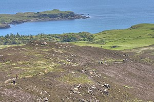 Eigg - Slope down to Galmisdale. The metalworking site is just beyond the prow, on the left
