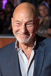A bald caucasian man at a film premiere with a closely cropped grey beard.