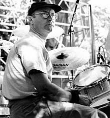 A middle-aged man, wearing a hat, glasses, light top, jeans and a wristbands, playing on a drumkit.