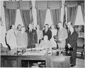 Photograph of President Truman signing the document implementing the North Atlantic Treaty at his desk in the Oval... - NARA - 200163.tif