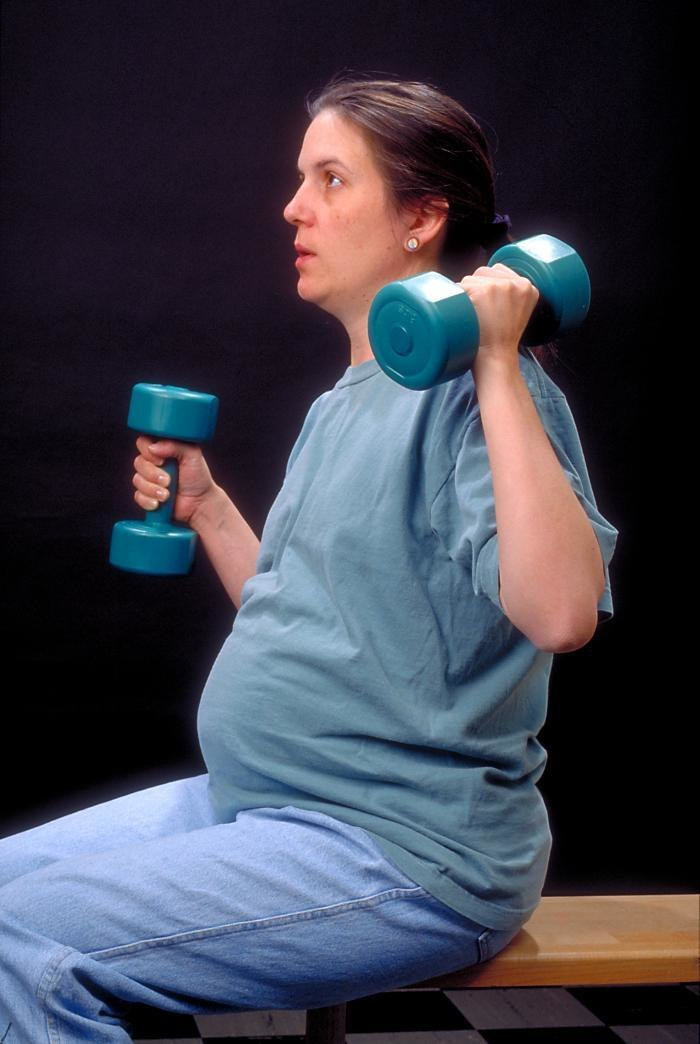 Pregnant Woman With Dumbells
