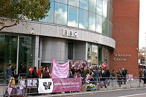 Banner-waving protesters in front of a building with BBC logo