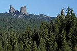 The Rabbit Ears, a pair of spires, rise above the coniferous forest of the Rogue River–Siskiyou NF.