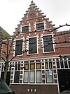 foto van Huis met brede trapgevel van het zgn. Haarlemse type rijk met natuurstenen blokken versierd; pui aangepast. Met tongewelf gedekte gang