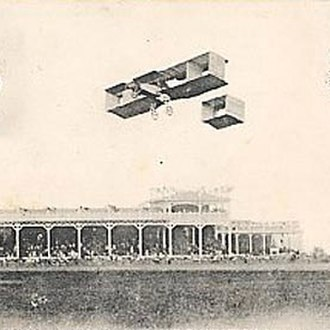 Raymonde de Laroche - A postcard photo claiming to show Raymonde de Laroche in flight in her Voisin biplane at the Grande Semaine d'Aviation de la Champagne Reims airshow in 1910, but actually showing an unknown Voisin biplane at the 1909 event, as obvious from the buildings