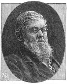 A bespectacled man with gray hair and a long beard wearing a black jacket and white shirt