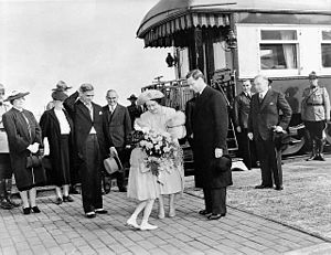 C. D. Howe - A little girl presents Queen Elizabeth (later the Queen Mother) with flowers as her husband the King (to her right), Prime Minister Mackenzie King (further to right) and Transport Minister C. D. Howe (centre, behind hat being held by man in front) look on. Port Arthur, 1939