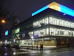 Exterior facade of the Ryerson Image Centre at night, with blue and yellow lights illuminating the top portion of the building