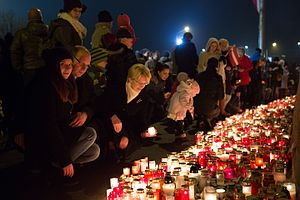 Lāčplēsis Day - People commemorating the fallen by placing candles on and by the wall of Riga Castle