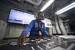 Sailor updates the hangar bay Ouija board in hangar bay control of USS Dwight D. Eisenhower. (27499952465).jpg