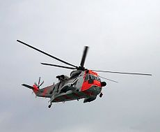 A red and white helicopter in the air.