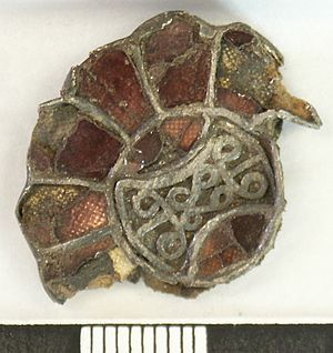Pointillé - Fragment of a composite silver disc brooch of rosette shape, with inlaid garnets and silver filigree ornament. Six of twelve trapezoidal cells are extant, each with a convex outer edge and set with a cloisonné garnet on pointillé gold foil.