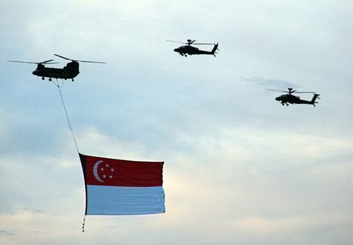A giant Singapore flag suspended from a CH-47 Chinook helicopter and accompanied by two Boeing AH-64D Longbow Apaches during a National Day Parade rehearsal on 29 July 2006. SingaporeFlag-NDPRehearsal-20060729.jpg