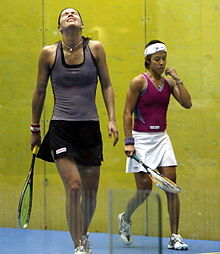 A female squash player in a bluish top throws back her head in annoyance while another squash player in a purple top and a white headband walks by