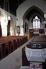 Intérieur d'une petite église simple, éclairé par un rayon de soleil. Un bénitier en pierre sculpté comportant une inscription illisible est aperçu au premier plan, sur la droite de l'allée centrale, devant les rangées de bancs en bois