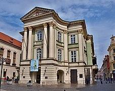 La façade d'un théâtre, à colonnade et fronton, entouré de rues piétonnes.