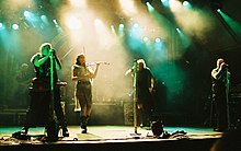 Four singers perform in the spotlights on stage. One is a female in shorts, a gauzy beige skirt and a leather belt, and plays the fiddle,  The males are wearing black sleeveless shirts, black pants and have military-looking gear. A rock band is in the background.