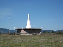 A thin up-pointing white cone with a cylindrical tip, a few meters tall, sits atop an elevated concrete platform, seen against clear blue sky; it is surrounded by a circle of about a dozen small picket-like vertical antennas