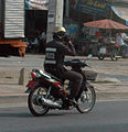 Thai Policeman on Motorbike with Cellphone - Pattaya Thailand.jpg