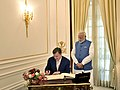 The Prime Minister of the Republic of Latvia, Mr. Maris Kucinskis signing the visitors' book, at Hyderabad House, in New Delhi on November 03, 2017. The Prime Minister, Shri Narendra Modi is also seen.jpg